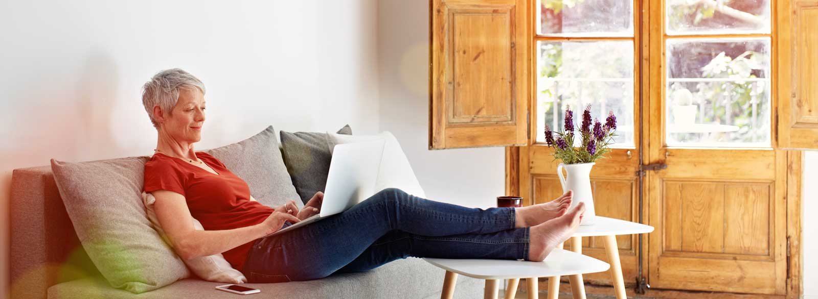 Woman uses laptop while relaxing on couch