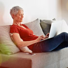 Woman types on laptop while relaxing on couch