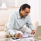 Man sits at laptop and pays her credit card bill Banner Online Banking and Bill Pay