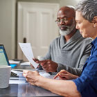 Older man and woman review financial statements to determine whether to open a Roth or Traditional IRA