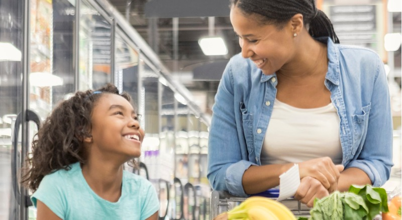 Mom and daughter shop at grocery store using their Banner Bank debit card