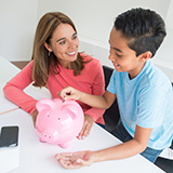 Mother teaching son about savings, boy inserting coins in pink piggy bank