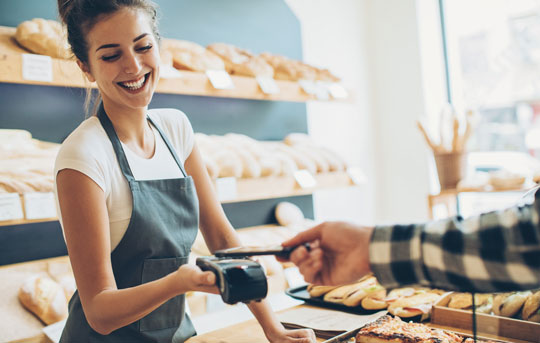 Woman in bakery accepts payment by mobile device