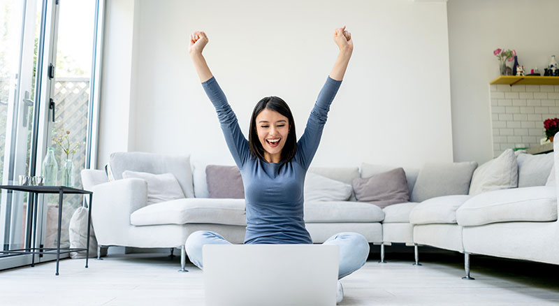 A woman throws her hands in the air excitedly in front of her computer