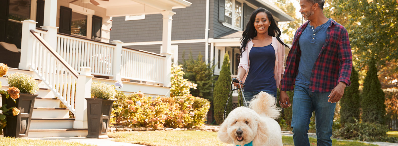 Couple walks dog through established neighborhood
