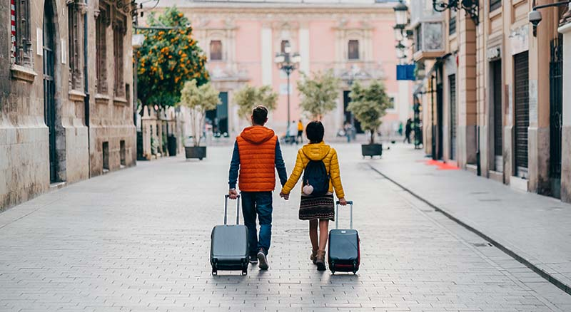 Couple walking with luggage in foreign country