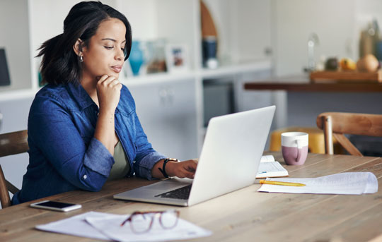 Woman sits at dining room table using laptop