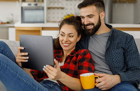 a couple relax on the couch and review their budget online