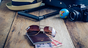 Travel essentials laid out on a wooden table - hat, sunglasses, camera, sunglasses, passport and foreign currency