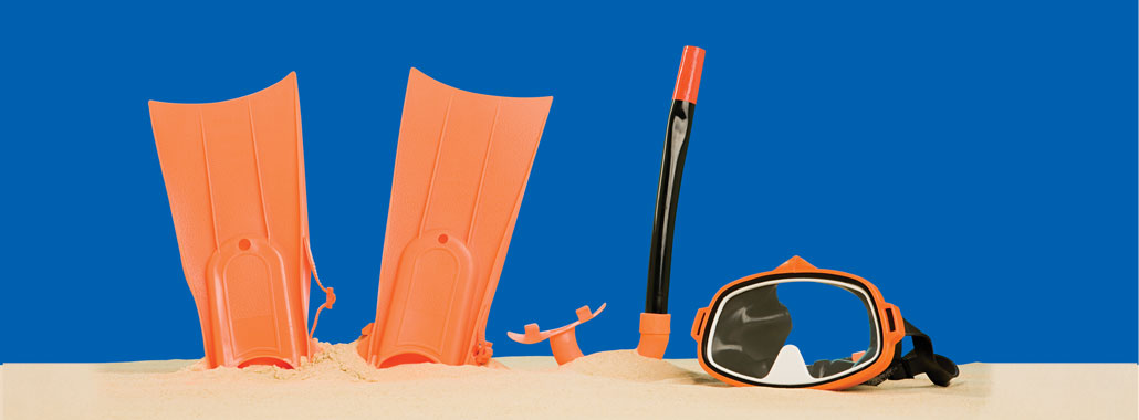 Mask, fins and snorkel sticking out of the sand
