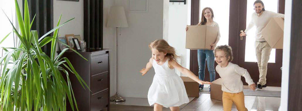 Parents carrying in boxes while children run into house