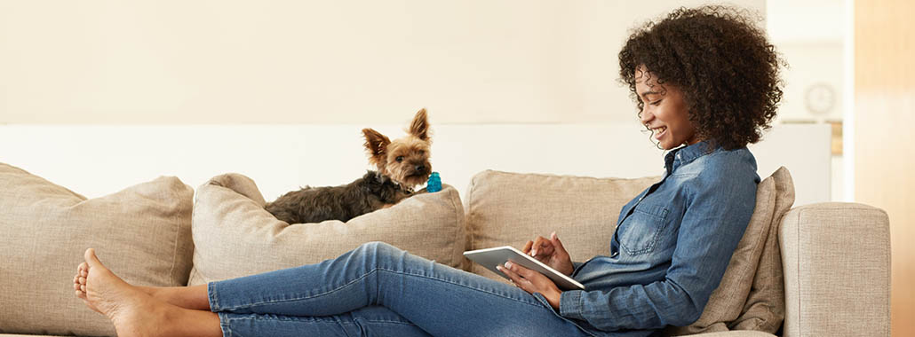 Person using PFM on tablet with dog on couch