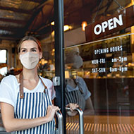 Owner with mask on opening shop