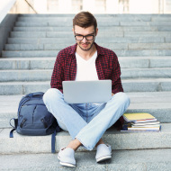 Student on steps with laptop and books