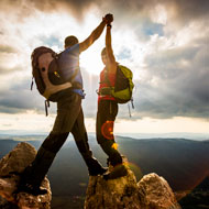 Man and woman high five after climbing to the top of the mountain