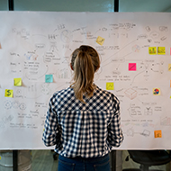 Woman looking at whiteboard and notes
