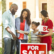 Family looking at paperwork with for sale sign