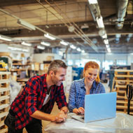 Man and woman in warehouse look at laptop screen