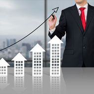 Business man in suit draws upward arrow above model buildings that increase in height