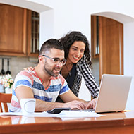 Couple looking at refinance options on laptop