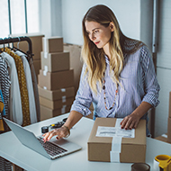 Woman on computer and packing up box to ship