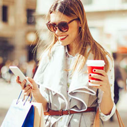 Shopper banks on mobile app while drinking coffee