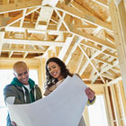 Man and woman review design plans while standing in a home construction financed by Banner Bank