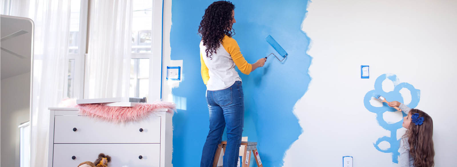 Mother and daughter painting bedroom