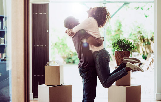Young couple hug and celebrate after moving into their new home, financed by Banner Bank