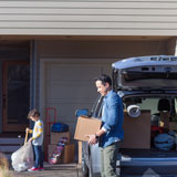 Father and son unpack car and move into their new home, financed by Banner Bank