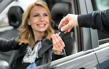 Blonde woman sitting in the driver seat of a car having the keys to the car handed to her