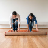 Man and woman unroll area rug onto wood floor