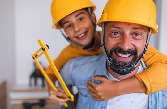 A father and young son in yellow hard hats smiling while working on improvements