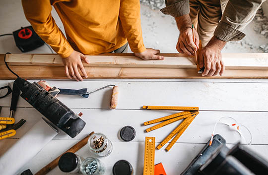 Two people measure wood for home improvements on a tool-covered table