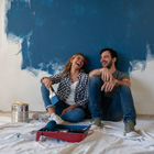 Couple takes a break from painting wall