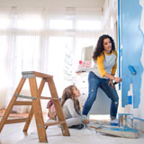 Mother paints bedroom blue with a roller brush while daughter looks on