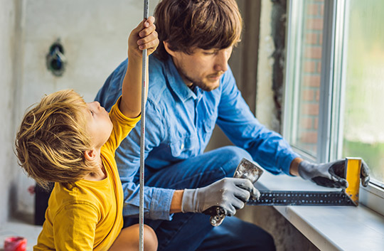 A father and child measure windows for renovations