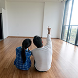 Couple on the floor of empty house looking at remodel options