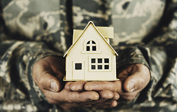 Military member holding cardboard house in their hands