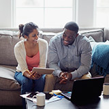 Couple looking at finances on tablet and laptop