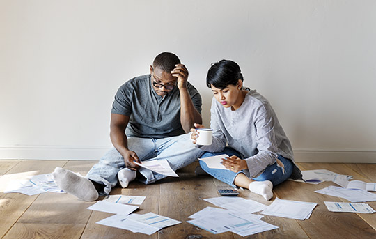 Couple looking at piles of bills on the floor