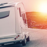 Recreational vehicle on mountain road at sunset