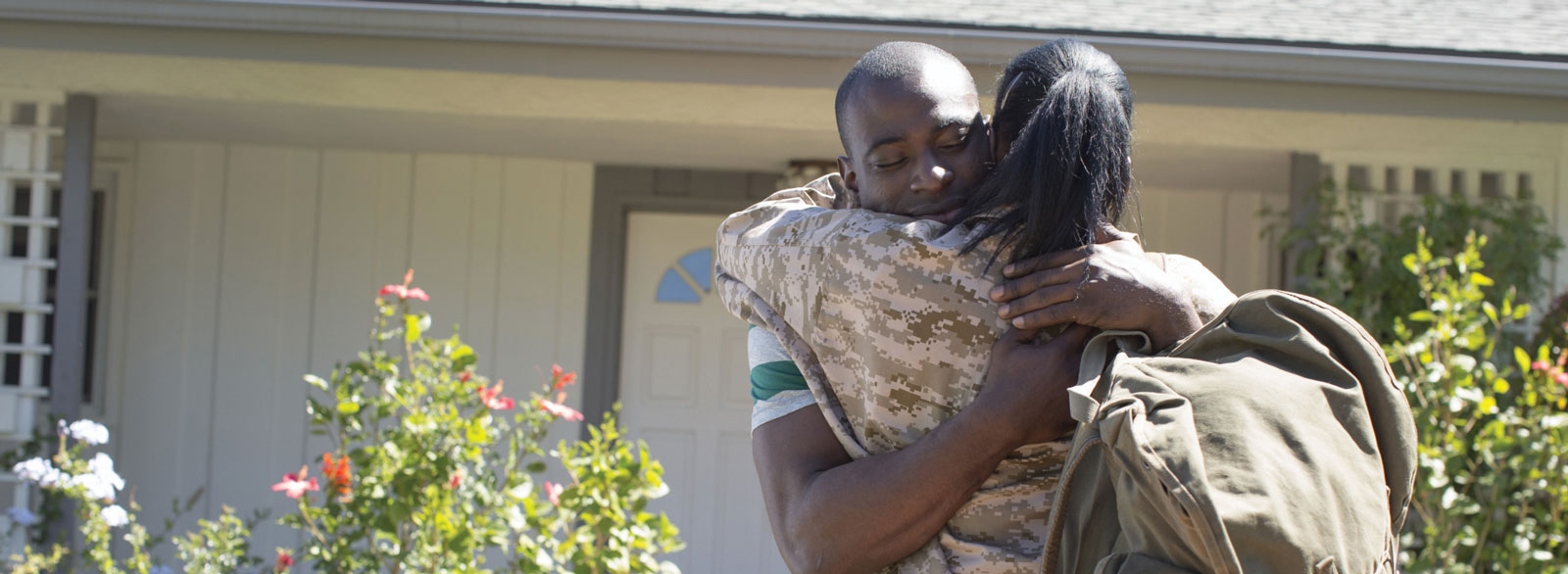 Man hugs woman, who is in military uniform