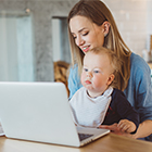 Photo of mom and baby at computer
