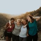 Four women hug while hiking