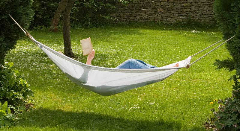 Person reading a book in a hammock on a sunny day