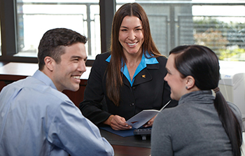 Hispanic couple sitting with a Hispanic female banker at a bankers desk the couple is looking at each other smiling
